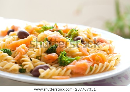 Delicious plate of pasta for lunch consisting of spiral pasta, broccoli, olive, smoke salmon in olive oil. - stock photo
