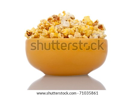 Delicious popcorn in yellow ceramic bowl over white background. - stock photo