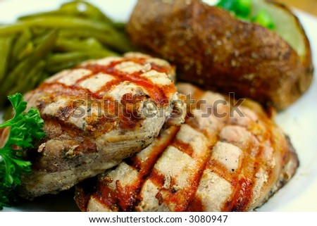 Delicious pork chop meal with a baked potato - stock photo