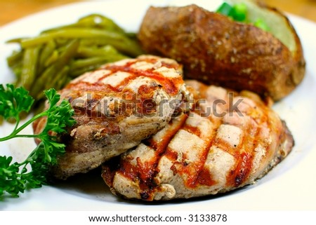 Delicious pork chop meal with a baked potato