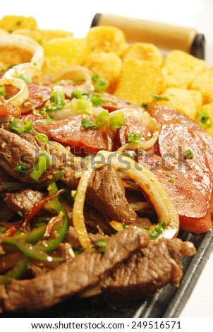 Delicious portion of  beef steak, sausage and potatoes served on a wooden kitchen board - stock photo