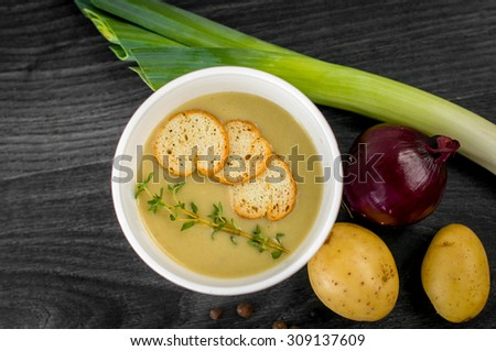 Delicious portion of cream soup with crackers and herbs - stock photo