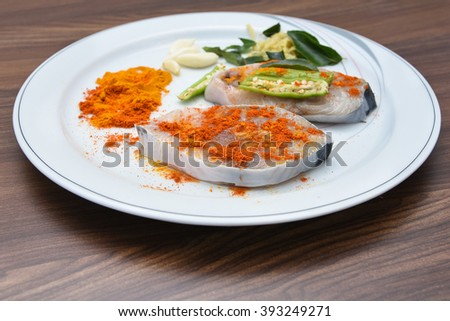 Delicious portion of fresh King fish fillet with aromatic herbs, spices and vegetables - healthy food, diet or cooking concept. Turmeric, chilly, curry leaf Kerala style fish curry preparation  - stock photo