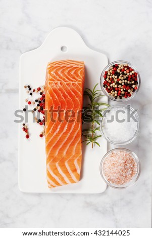 Delicious portion of fresh salmon fillet with aromatic herbs and spices - healthy food, diet or cooking concept. Top view. - stock photo