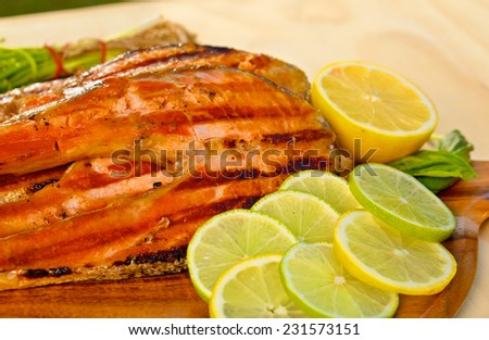 Delicious  portion of fresh salmon fillet with lime cooked on a grill or BBQ