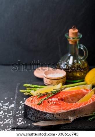 Delicious portion of fresh salmon steak with aromatic herbs, spices and vegetables on black background - healthy food, diet or cooking concept