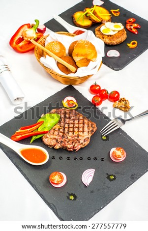 Delicious portion of healthy grilled lean medium rare beef steak cut through and served on a board garnished with fresh herbs and bread - stock photo