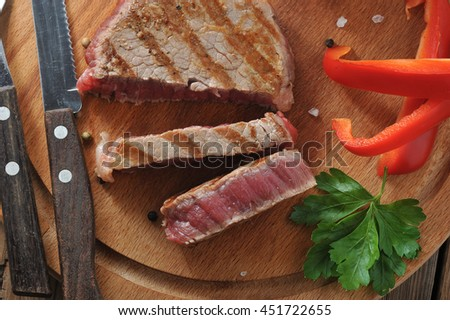 Delicious portion of healthy grilled lean medium rare beef steak cut through and served on a wooden kitchen board - stock photo