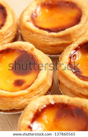 delicious portuguese egg tart on wooden texture table - stock photo