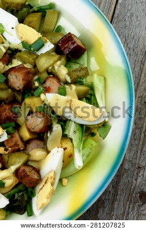 Delicious Potato and Sausage Salad with Gherkins, Lettuce, Boiled Eggs and Mustard Sauce closeup on Yellow and Blue Plate closeup on Rustic Wooden background - stock photo