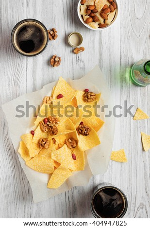 Delicious potato chips, cola nuts and cheese on a light background - stock photo