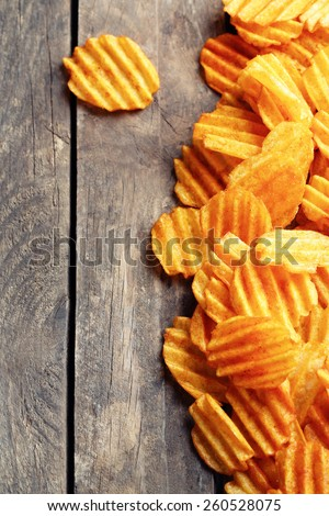 Delicious potato chips on wooden table close-up - stock photo