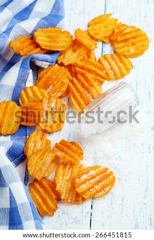 Delicious potato chips with salt on wooden table close-up - stock photo