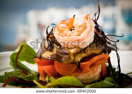 Delicious prawn starter with salad, aubergine and tomato. - stock photo