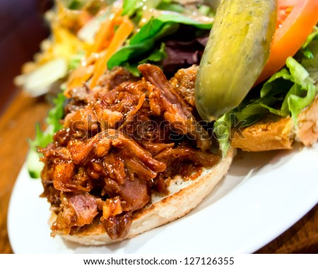 Delicious pub style pulled pork sandwich with pickle and salad on the side