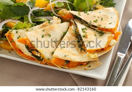 Delicious pumpkin quesadilla sliced and ready to serve with a garden salad. - stock photo