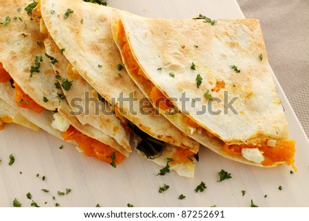 Delicious pumpkin quesadilla sliced and ready to serve with chopped parsley. - stock photo