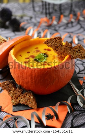 delicious pumpkin soup with halloween decoration