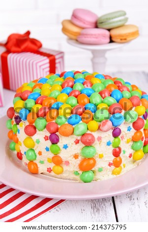 Delicious rainbow cake on plate on table on bright background - stock photo