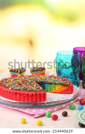 Delicious rainbow cake on table, on bright background - stock photo