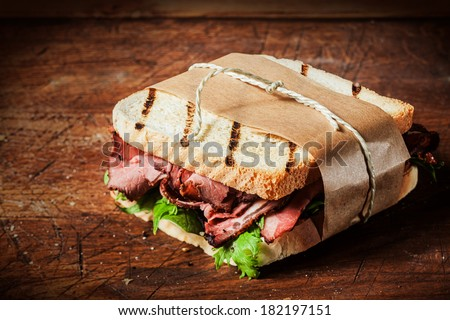 Delicious rare roast beef sandwich on grilled toast wrapped in brown paper tied with string served on a wooden counter in a rustic bistro - stock photo