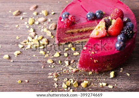 Delicious raspberry cake with fresh strawberries, raspberries, blueberry, currants and pistachios on wooden background.  - stock photo