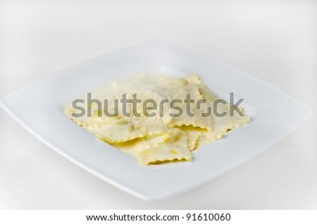 Delicious ravioli with creamy sauce on white background - stock photo