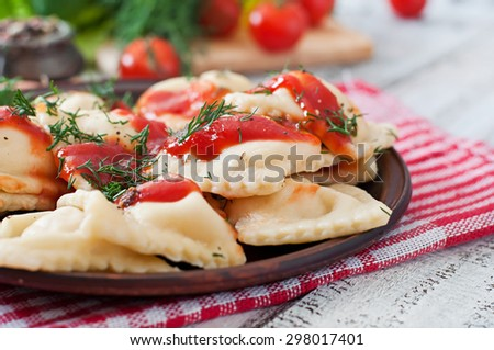 Delicious ravioli with tomato sauce and dill - stock photo