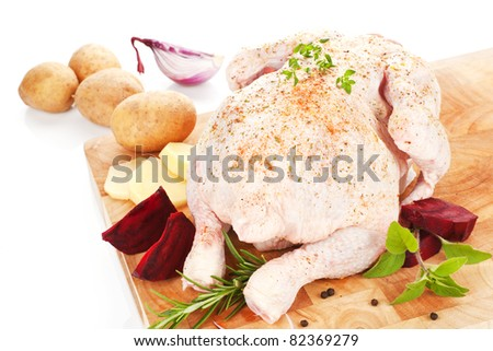 Delicious raw chicken on wooden board with fresh vegetable and herbs prepared for cooking. - stock photo