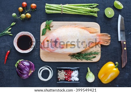 Delicious raw fish, fresh vegetables, herbs and spices on a dark background. Diet / healthy food concept.  - stock photo