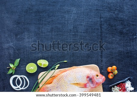 Delicious raw fish (Nile tilapia) with lime, herbs and spices. Cherry tomato and onion rings. Dark background. Copy space.  - stock photo