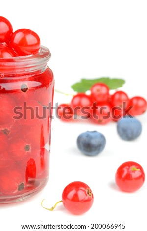 Delicious raw red currants in a small jar with assorted berries around isolated on white background - stock photo