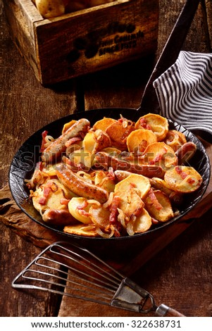 Delicious recipe with crispy fried sliced potatoes, grilled Nuremberger bratwurst and bacon served in a frying pan in a rustic kitchen, high angle view - stock photo