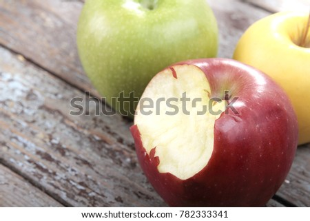 Delicious Red Apple,  golden yellow apple and diet green apple on rustic damaged wood background. Copy Space for text area. Three beautiful different variation colors of apples.