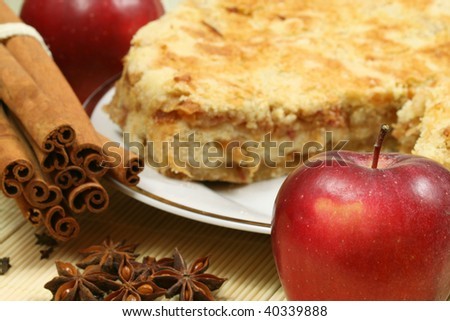 Delicious red apple in the foreground and cinnamon sticks with apple pie in background