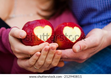 Delicious red apple with symbolic heart cutout on rough in hands