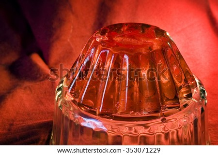 Delicious red gelatin, jelly dessert like pudding close-up on red background - stock photo