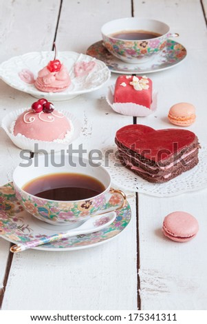 Delicious red heart cake with several cakes and two cups of coffee