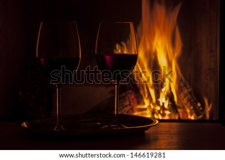delicious red wine at fireplace natural light only - stock photo