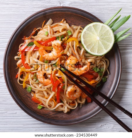 Delicious rice noodles with shrimp and vegetables close-up on a plate. top view  - stock photo