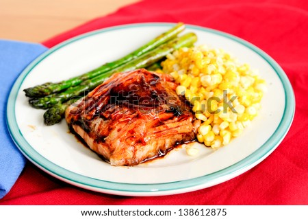 delicious rice paper wrapped salmon with ginger and carrot in a sweet glaze and fresh vegetables - stock photo