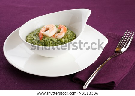 Delicious rice with spinach, greens and shrimps. Served in a modern dishware over a violet table setting