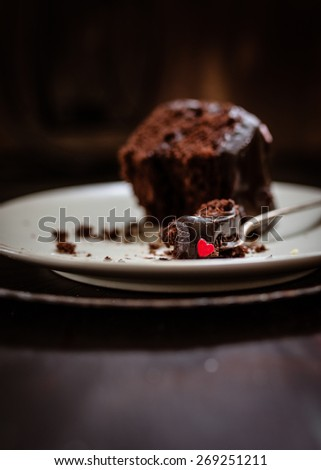 Delicious rich chocolate cake with dark ganache and little red sugar heart. Selective focus. - stock photo