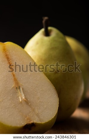 delicious, ripe pears on a wooden kitchen table, black background, closeup, vertical. - stock photo