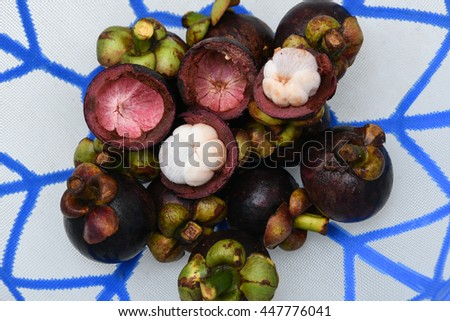 Delicious ripe purple mangosteen. sweet and tangy, juicy Queen of fruits cut open/cross section showing the thick purple skin and white flesh. - stock photo