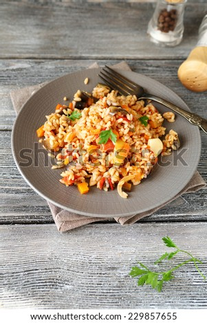Delicious Risotto with peppers, carrots and tomatoes on a plate on boards - stock photo
