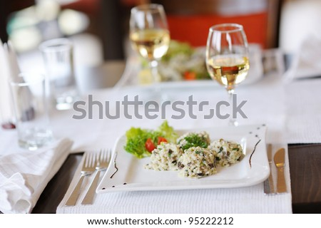 Delicious risotto with tomato and lettuce on a white plate