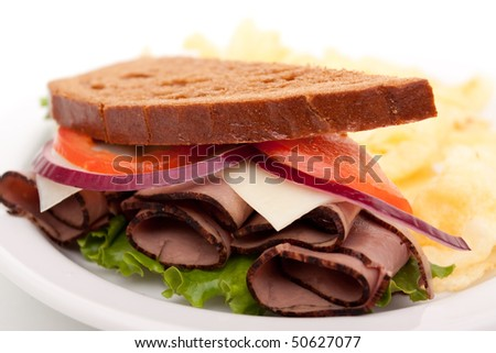 Delicious roast beef sandwich platter with whole wheat bread and potato chips - stock photo