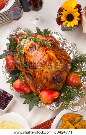 Delicious roasted turkey with savory vegetable side dishes in a fall theme - stock photo