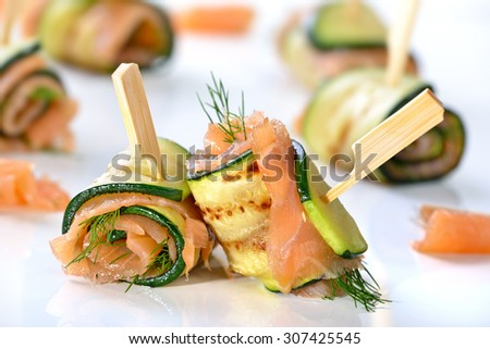 Delicious rolls of fried zucchini slices and smoked salmon with dill - stock photo